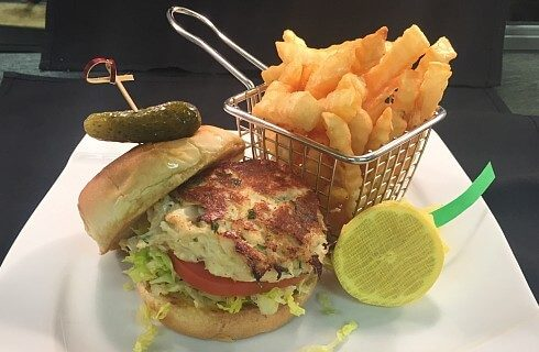 Grilled crabcake on a bun with lettuce and tomato next to a basket of fries on a white square plate