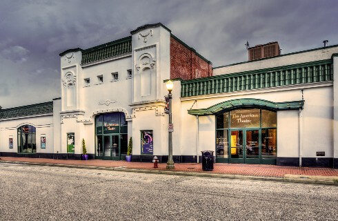 Large white theatre building with green doors, awning and accents on an empty street