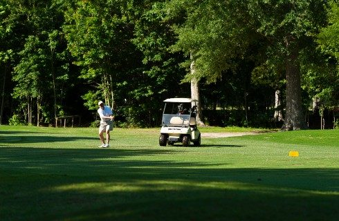 Golfer in shorts mid-swing out on a wooded golf course with a cart nearby
