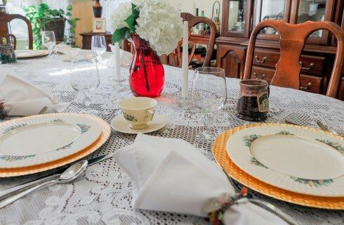 Dining table set with fine china on gold charger plates and a red vase with white flowers