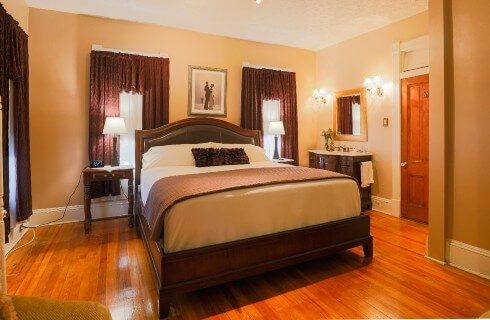 Large guest room with king bed, three windows, vanity with sink and hardwood floors