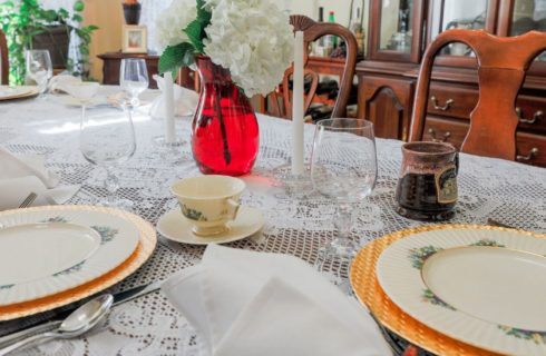 Dining table with lace tablecloth and fine china, gold charger plates and white linens