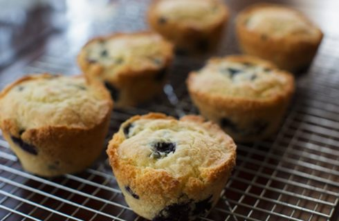 Six perfectly golden brown blueberry muffins on top of a cooling rack
