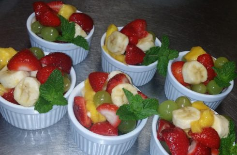 Six white ramekins filled with mixed fruit and min leaves on a silver countertop