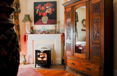 Vintage fireplace with electric firebox next to a large brown armoire with mirrored front