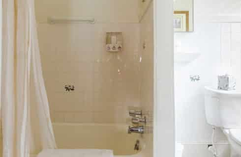Bright white bathroom with tiled shower and tub and toilet next to a window