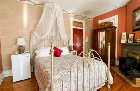 Four-poster brass-style bed with net canopy in room with fireplace, armoire and small fridge