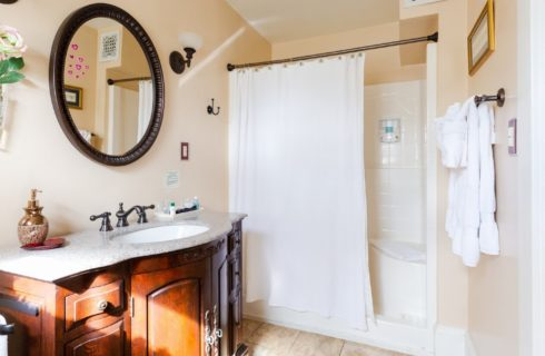 Bright bathroom with stand up shower, white curtain and dark brown vanity with sink and oval mirror