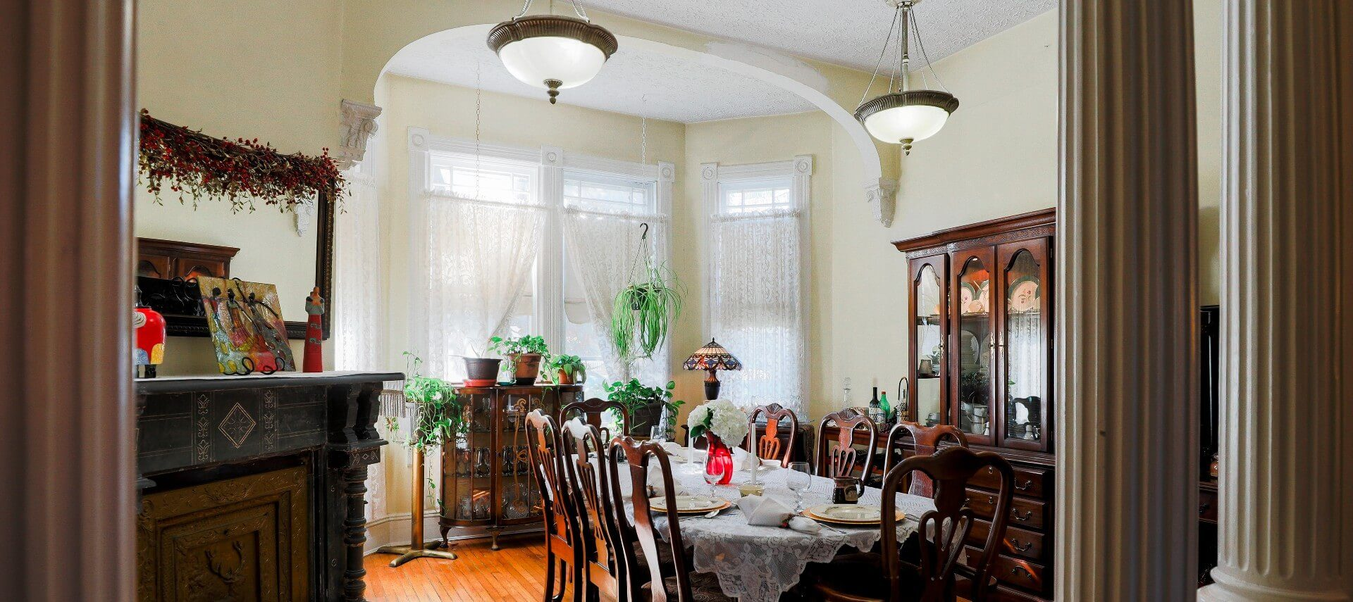 Large dining room with antique table and hutch and bay window with three large windows
