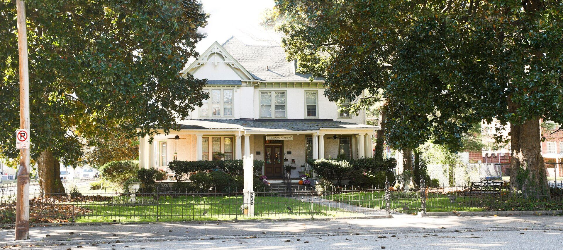 Front facing view of a beautiful white home with large front porch, white columns and wrought iron fence around yard