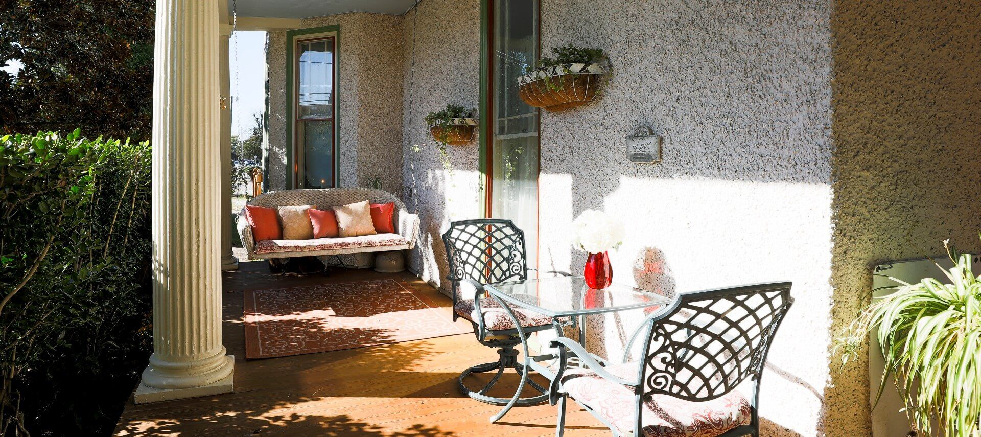 Outside patio of a home with hanging loveseat and wrought iron table with two chairs