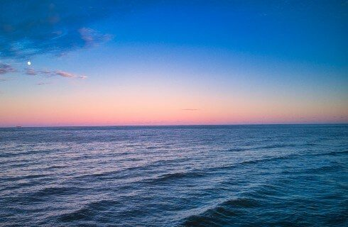 View of the ocean at sunset with soft waves and a blue, yellow, and pink sky