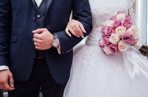 Bride in white with bouquet of white and pink flowers arm in arm next to a groom in a black suit