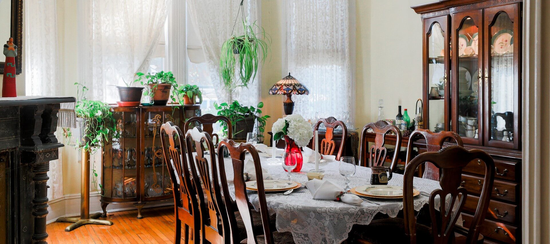 Large dining room with hutches and antique table and 8 chairs, set with lace tablecloth and fine china