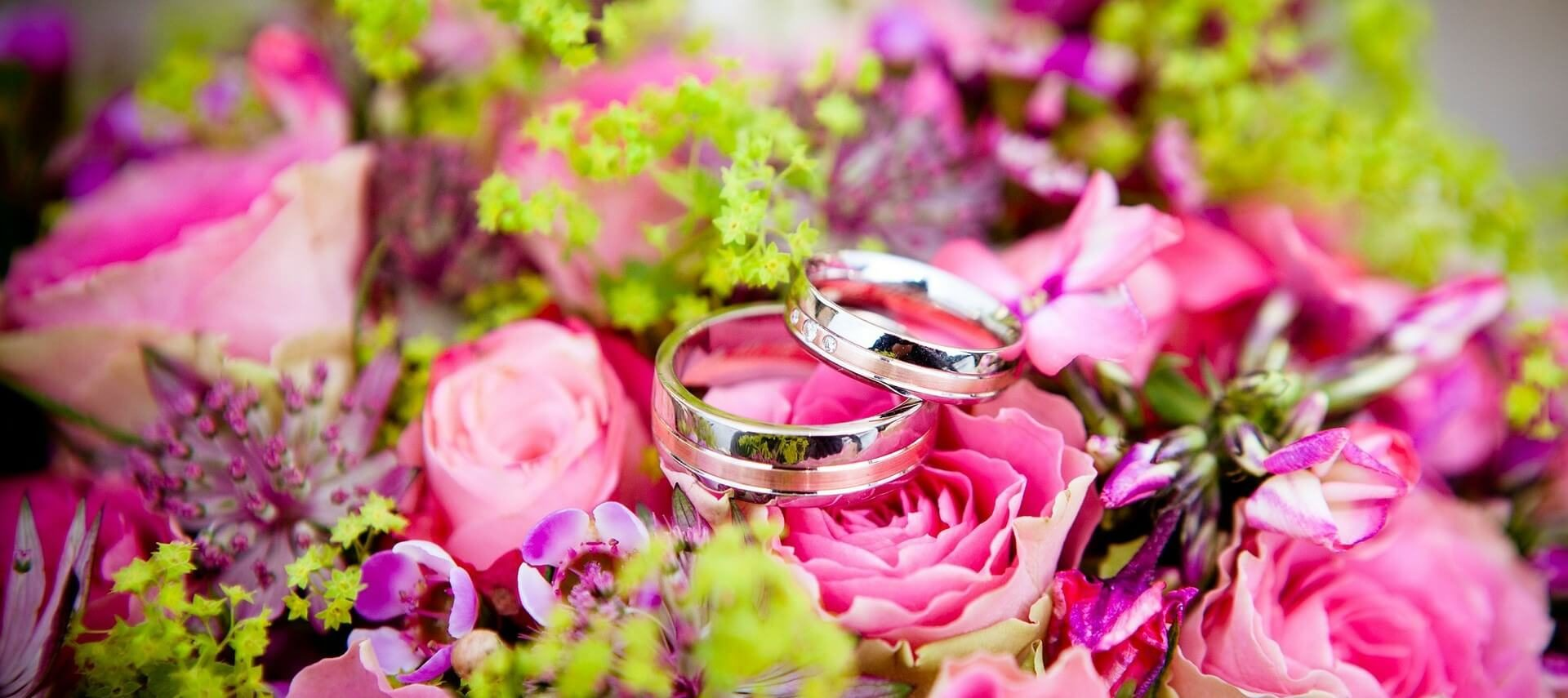 Two silver wedding rings sitting atop a bright pink and purple bouquet of flowers with green springs